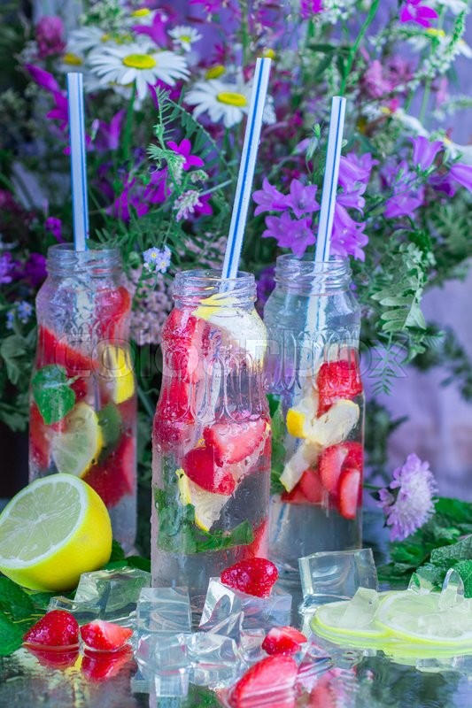 Stock image of 'Homemade lemonade. Summer refreshing drink of strawberries, lemon, lime and mint with ice'