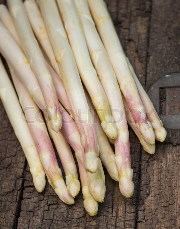 Stock image of 'Fresh white asparagus on an old wooden table. Shallow depth of field'