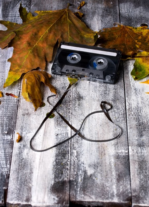 Stock image of 'Old audio cassette lying among fallen leaves on the rough table'