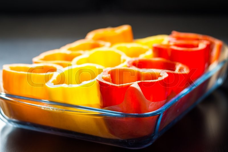 Stock image of 'Red, orange and yellow peppers getting prepared for cooking in a dish in the kitchen'
