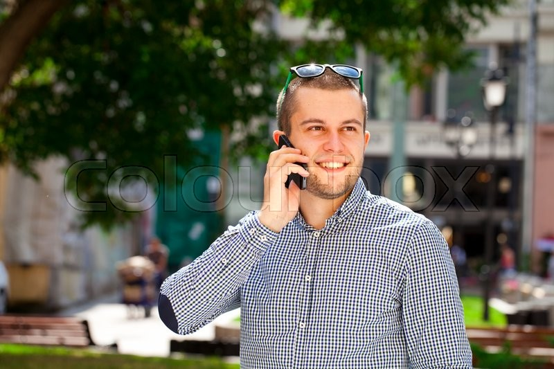 Stock image of 'happy men calling by phone in summer street'