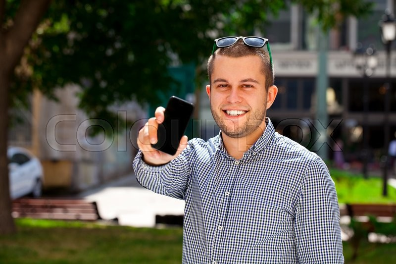 Stock image of 'Happy young man shows a mobile phone screen in summer street'