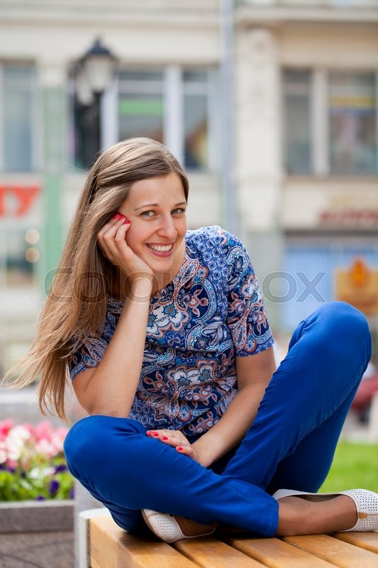 Stock image of 'Happy Beautiful young woman sits on a bench in a summer street'