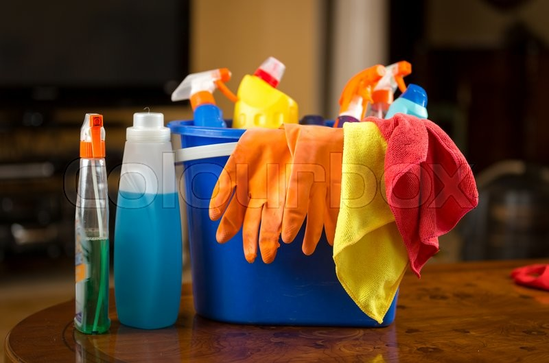 Stock image of 'Closeup photo of cleaning chemicals, gloves and rags lying in plastic bucket'