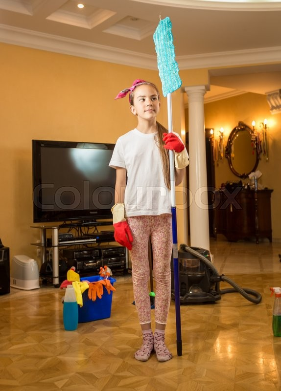 Stock image of 'Funny shot of teenager girl cleaning room and posing with swab'