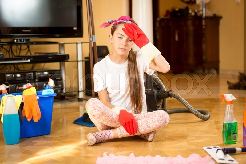 Stock image of 'Portrait of tired teenager girl cleaning wooden floor at living room'