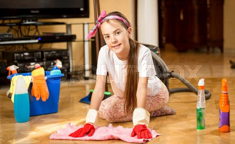 Stock image of 'Cute smiling teenage girl cleaning up living room and washing wooden floor'