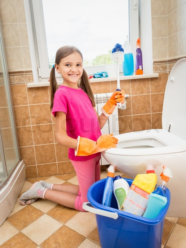 Stock image of 'Cute smiling girl cleaning toilet with brush'