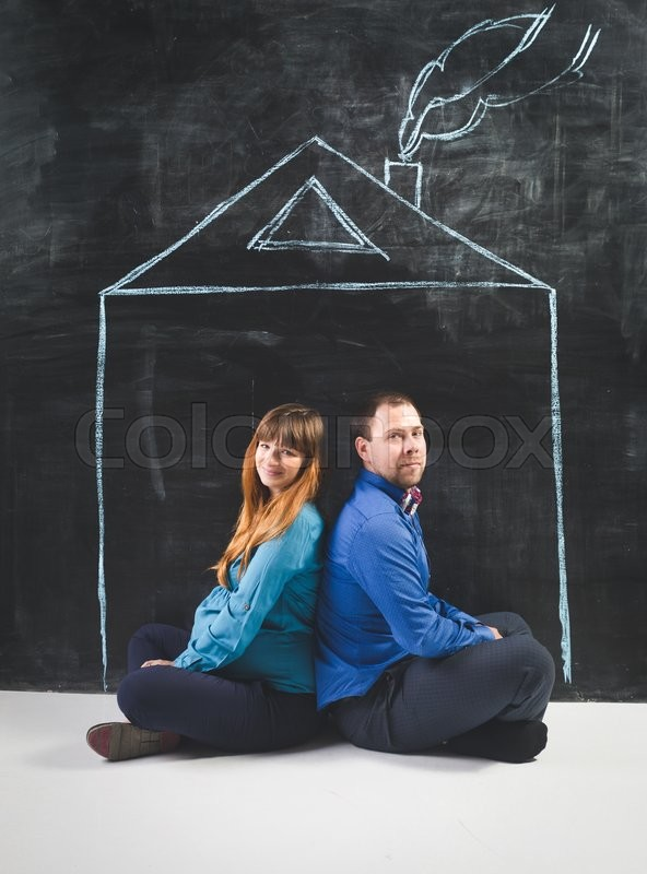 Stock image of 'Concept photo of pregnant woman and husband posing at house drawn on chalkboard'
