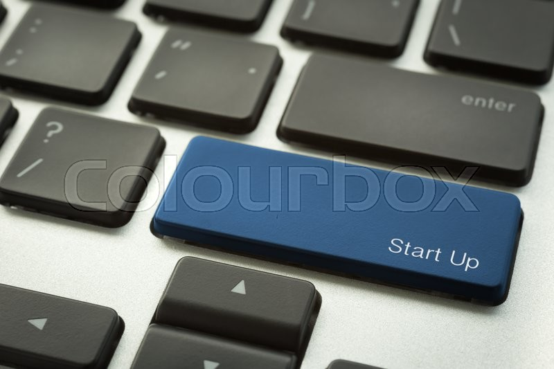 Stock image of 'Close up laptop keyboard focus on a blue button with typographic word START UP. Business and education concepts.'