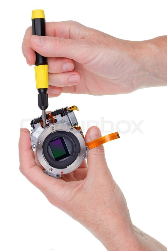Stock image of 'The engineer repairs the optical electronic device. Isolated'