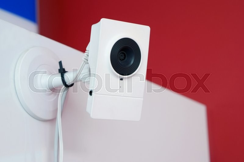 Stock image of 'The big brother watches you concept. The mass production white camera of video  supervision is fixed on a wall of office. Art soft selective focus'