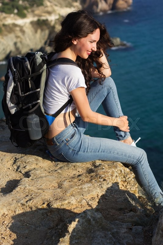 Stock image of 'Pretty traveler girl is sitting on rock edge with backpack '