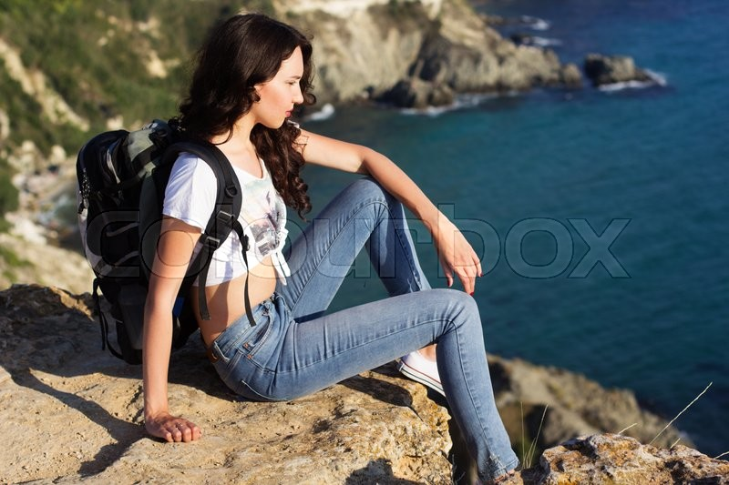 Stock image of 'Pretty traveler girl is sitting on rock edge over sea background  with backpack, summer time'