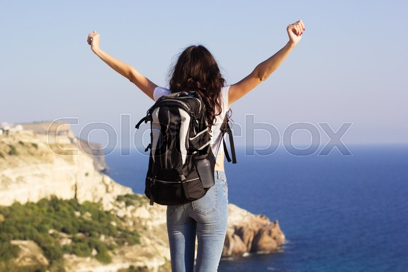 Stock image of 'Back view of young pretty slim woman standing with backpack on cliff's edge and looking into sea'