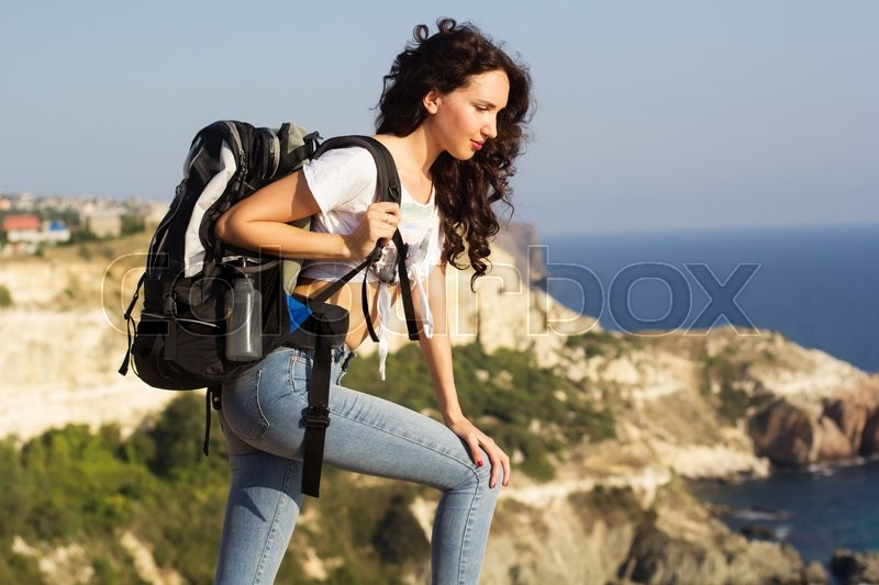 Stock image of 'Girl traveler is sitting on rock with backpack'