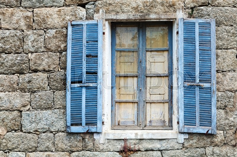Stock image of 'Old window with blue open shutters in rural ancient gray stone wall, background texture'