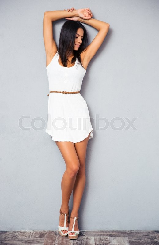 Stock image of 'Full length portrait of a beautiful woman in fashion dress standing in studio'