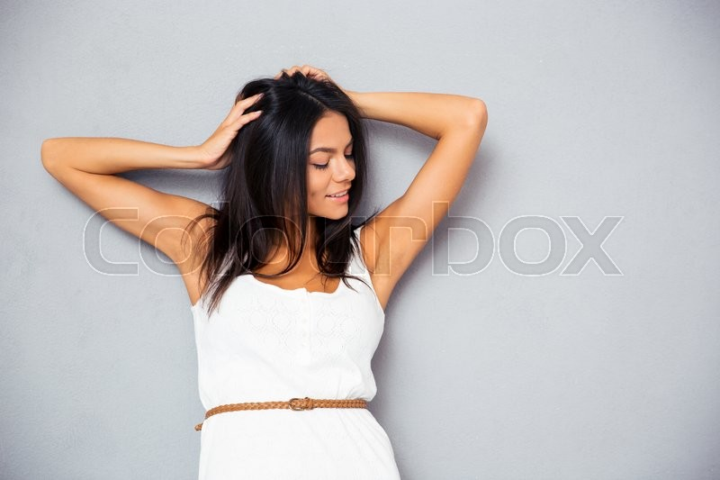 Stock image of 'Portrait of a smiling young woman touching her hair over gray background'