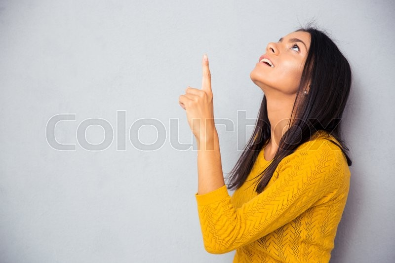Stock image of 'Pensive woman showing finger up over gray background'