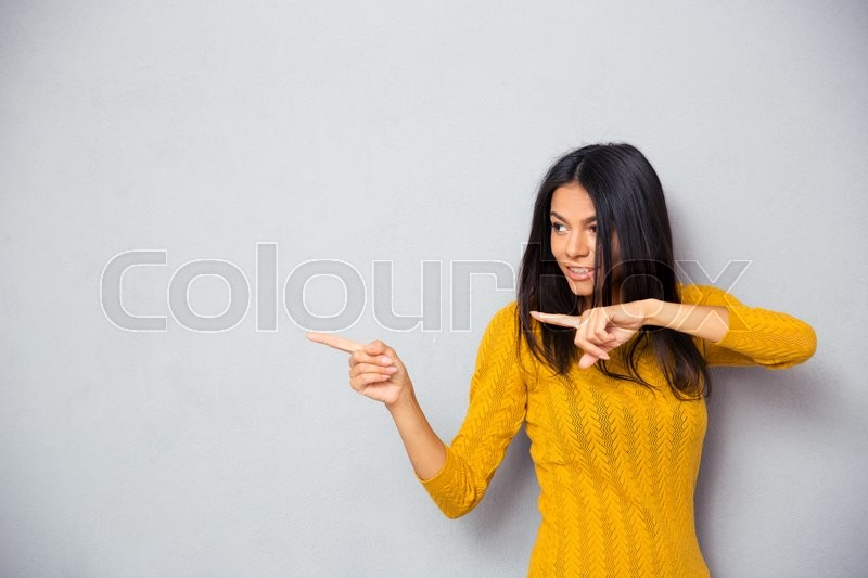 Stock image of 'Happy woman in sweater showing finger away over gray background'