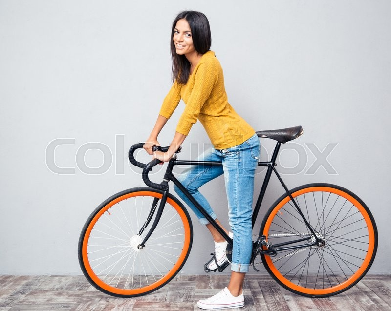 Stock image of 'Full length portrait of a smiling woman with bicycle on gray background. Looking at camera'