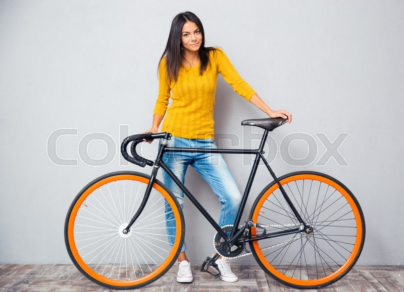 Stock image of 'Full length portrait of a happy woman standing near bicycle on gray background. Looking at camera'