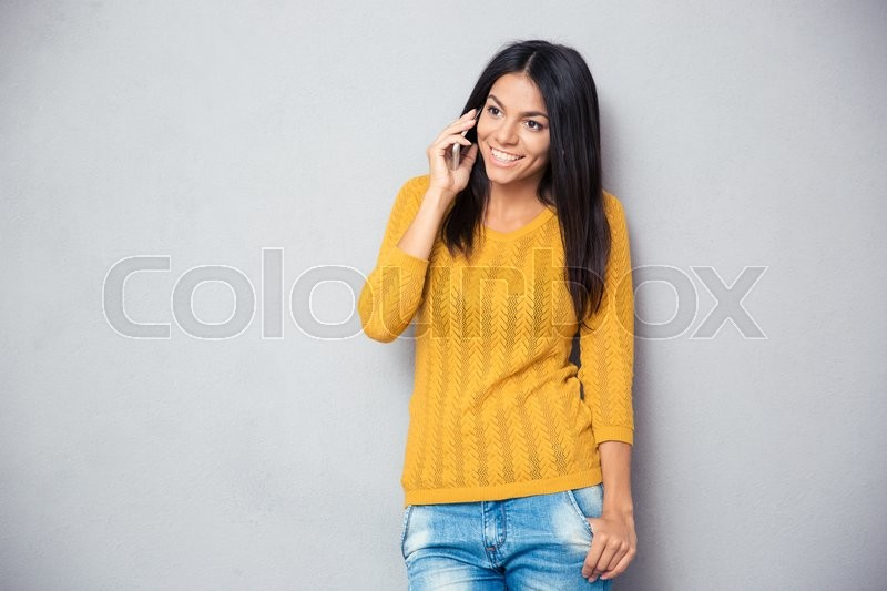 Stock image of 'Happy young woman talking on the phone over gray background'