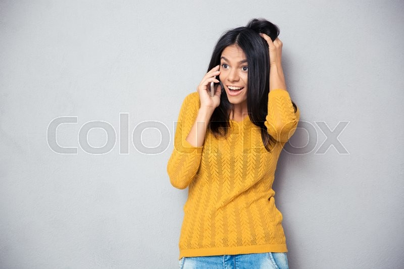 Stock image of 'Amazed young woman talking on the phone over gray background'