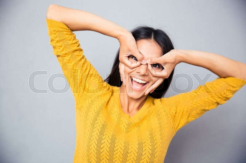 Stock image of 'Laughing woman looking at camera through fingers over gray background'