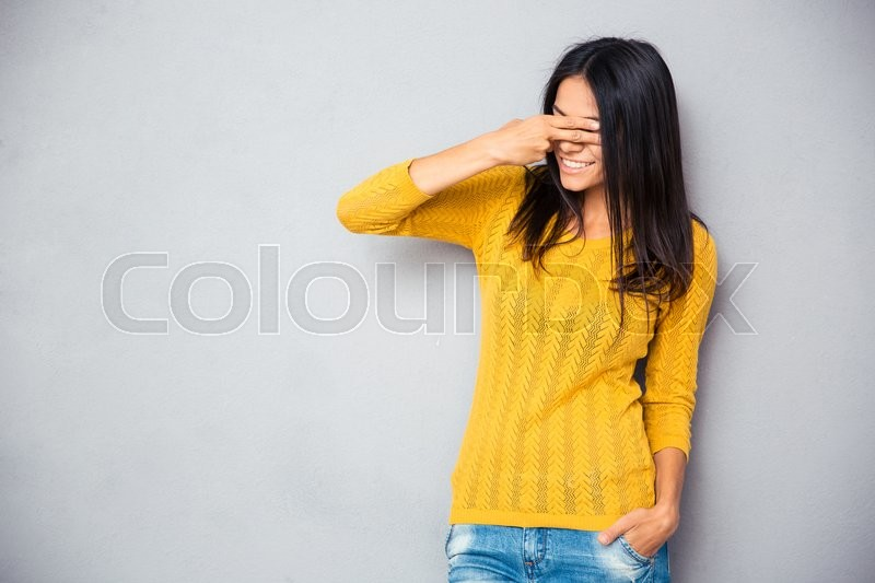 Stock image of 'Smiling young woman covering her eyes with fingers over gray background'