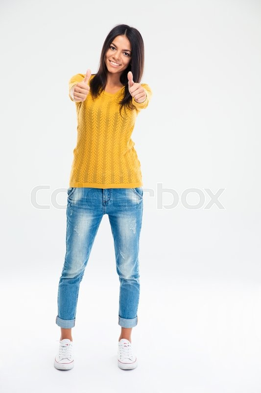 Stock image of 'Full length portrait of a smiling young woman showing thumbs up isolated on a white background'