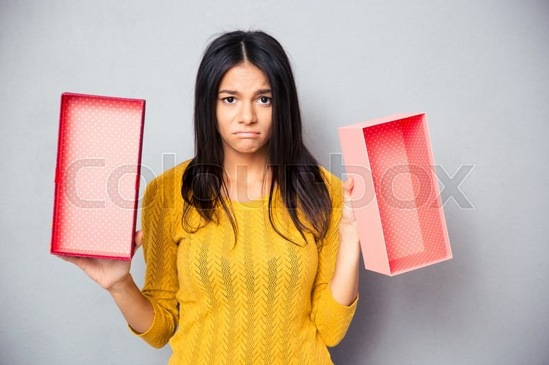 Stock image of 'Unhappy woman holding empty gift box over gray background. Looking at camera'