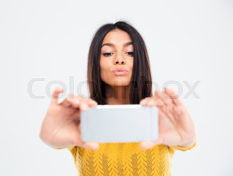 Stock image of 'Happy beautiful woman making selfie photo on smartphone isolated on a white background'