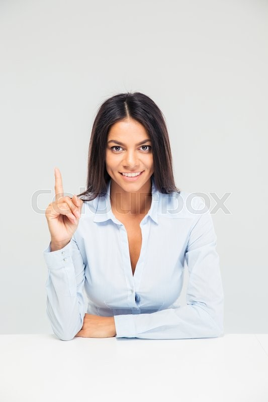 Stock image of 'Businesswoman sitting at the table and pointing finger up isolated on a white background'
