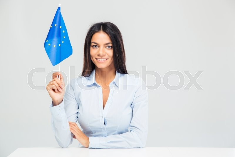 Stock image of 'Happy businesswoman sitting at the table with european flag isolated on a white background. Looking at camera'