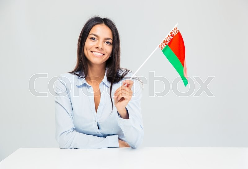 Stock image of 'Happy businesswoman sitting at the desk and holding american flag isolated on a white background'