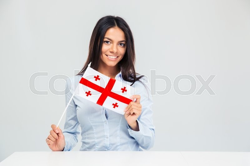 Stock image of 'Smiling young woman sitting at the table with georgian flag isolated on a white background. Looking at camera'