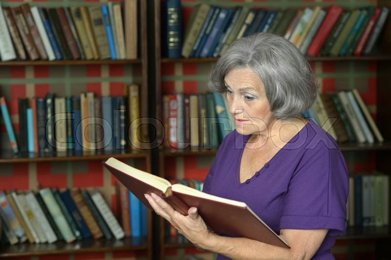 Stock image of 'Portrait of a beautiful elderly woman with book'