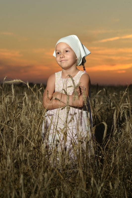 Stock image of 'Cute little  girl in the wheat field on sunset'