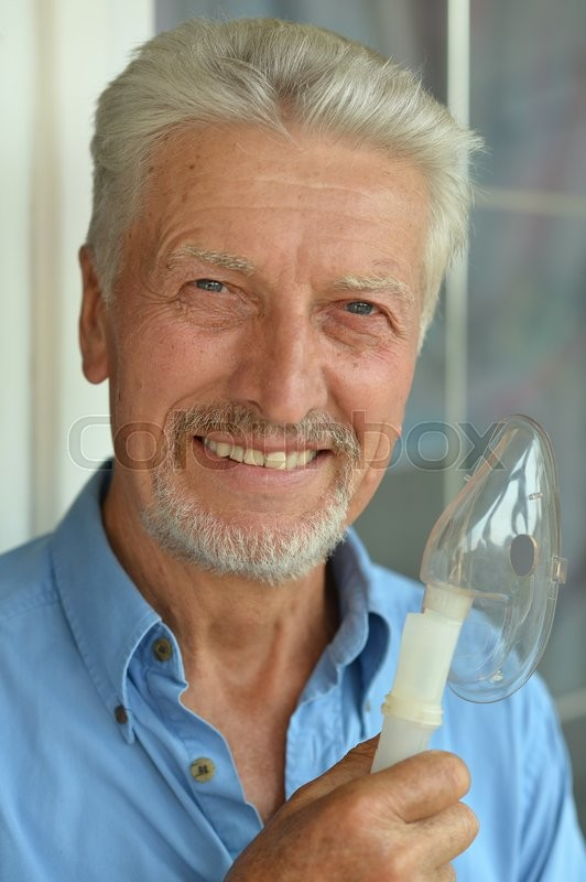 Stock image of 'Portrait of elderly man with flu inhalation'