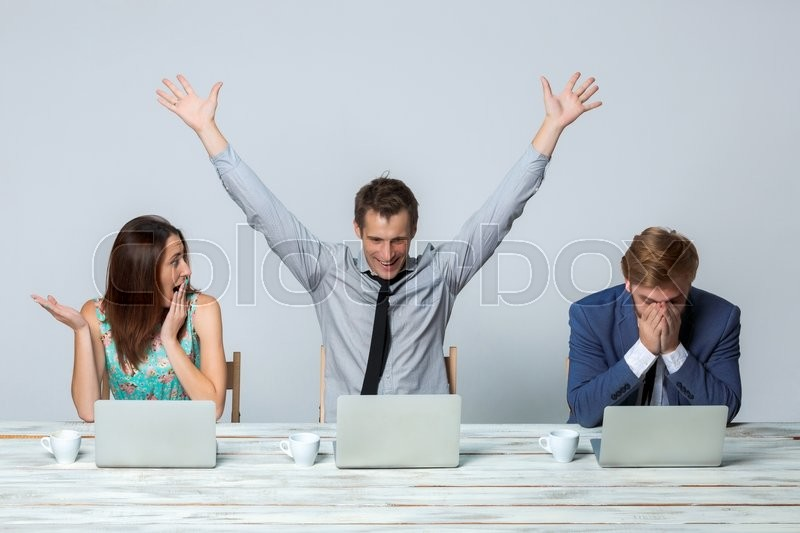 Stock image of 'Business team working together at office on light gray background. all working on laptops. One man raising his arms enjoying good idea'
