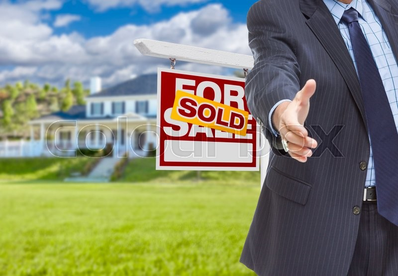 Stock image of 'Real Estate Agent Reaches for Handshake with Sold Sign and New House Behind.'