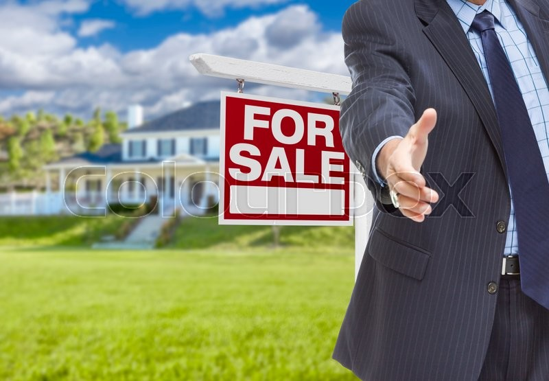 Stock image of 'Real Estate Agent Reaches for Handshake with Sale Sign and New House Behind.'