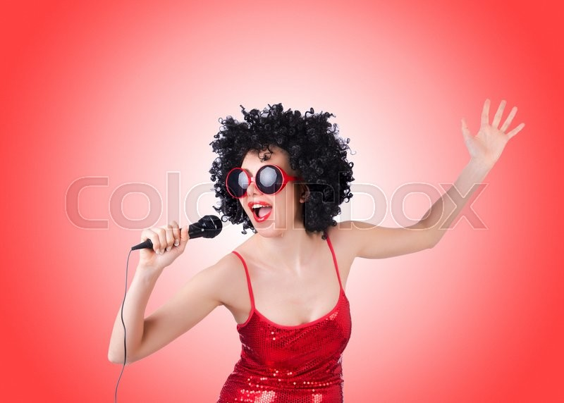 Stock image of 'Pop star with mic in red dress against gradient '