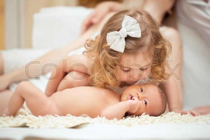 Portrait of a newborn baby with being kissed by big sister, stock photo