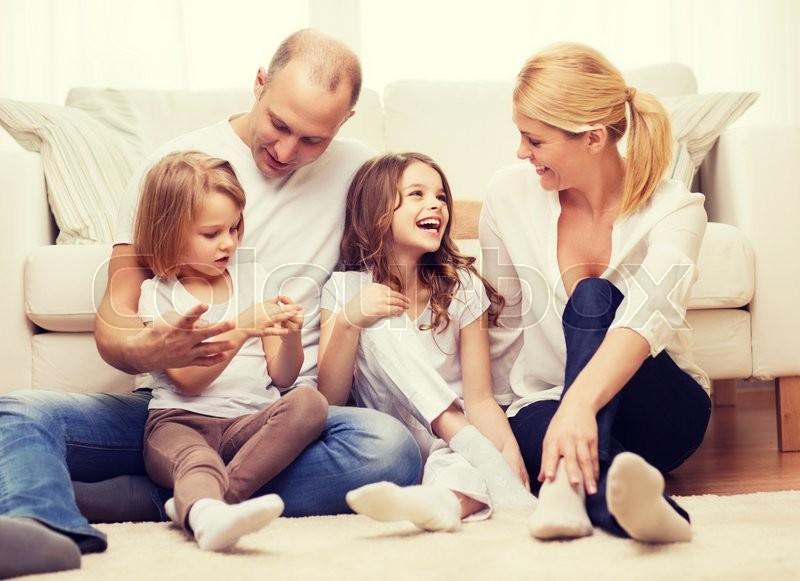 Family, children and home concept - smiling family with and two little girls sitting on floor at home, stock photo