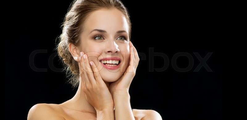 People, emotions and expressions concept - happy excited woman face over black background, stock photo