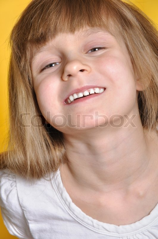 Stock image of 'Naughty smiling little girl . Yellow background.'