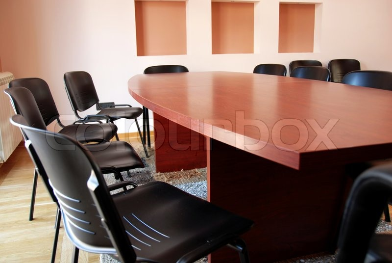 Stock image of 'Brown office meeting desk and black chairs indoor'